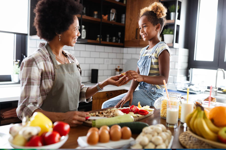 Personal Insurance - Mother and Daughter in the Kitchen Making Food Together